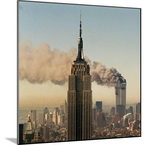Twin Towers of the World Trade Center Burn Behind the Empire State Buildiing, September 11, 2001--Mounted Photographic Print