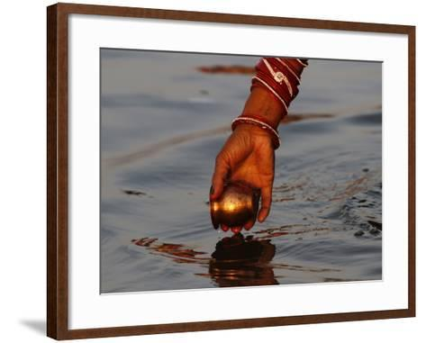 Woman Praying on the Banks of the River Ganges Fills Water into a Copper Vessel for a Ritual--Framed Art Print