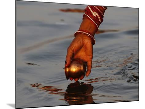 Woman Praying on the Banks of the River Ganges Fills Water into a Copper Vessel for a Ritual--Mounted Photographic Print