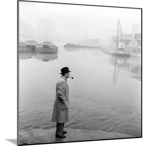 Georges Simenon Smoking a Pipe by the Navigli in Milan--Mounted Photographic Print