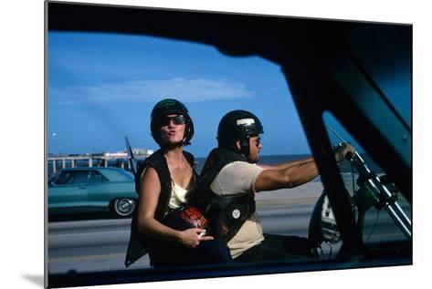 A Young Biker Sitting on the Motorbike Saddle with His Companion-Mario de Biasi-Mounted Photographic Print