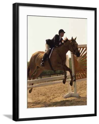 Side Profile of a Woman Riding a Horse Over a Hurdle--Framed Art Print