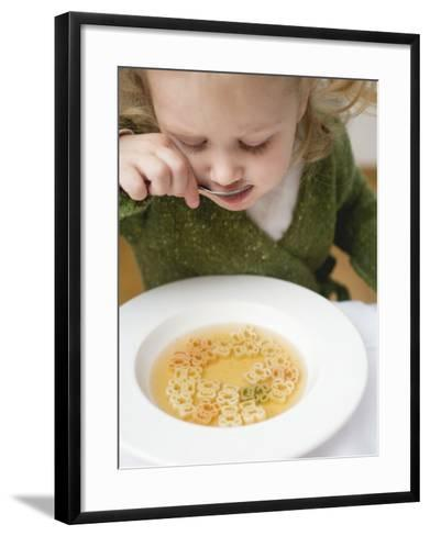 Small Girl Eating Soup with Teddy Bear Pasta--Framed Art Print