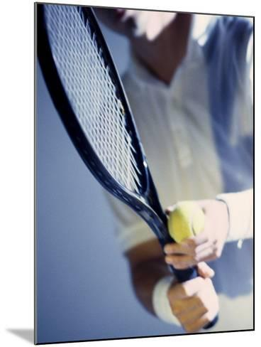 Close-up of a Young Man Holding a Tennis Racket and a Tennis Ball--Mounted Photographic Print