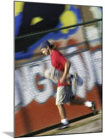 Young Man Running with Skateboard--Mounted Photographic Print