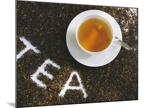 Cup of Black Tea, Surrounded by Tea Leaves with the Word Tea--Mounted Photographic Print