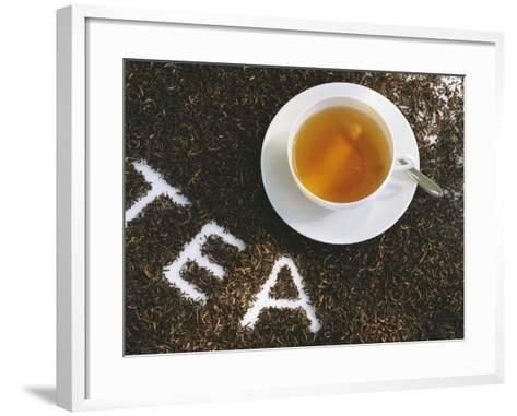 Cup of Black Tea, Surrounded by Tea Leaves with the Word Tea--Framed Art Print