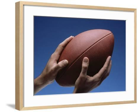 Hands Holding Football with Blue Background--Framed Art Print