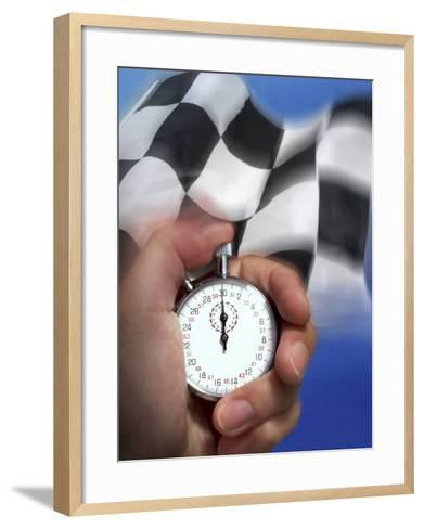 Person's Hand Holding a Stopwatch in Front of a Checkered Flag--Framed Art Print