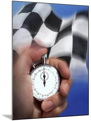 Person's Hand Holding a Stopwatch in Front of a Checkered Flag--Mounted Photographic Print