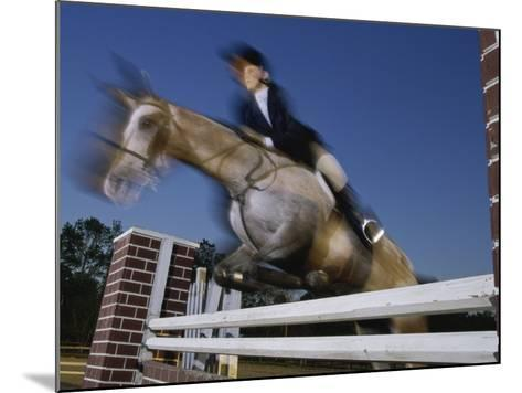 Low Angle View of a Woman Riding a Horse Over a Hurdle--Mounted Photographic Print
