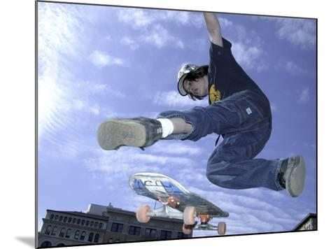Skateboarder in Midair Doing a Trick--Mounted Photographic Print