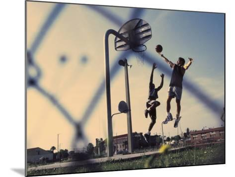 Low Angle View of Two Men Playing Basketball--Mounted Photographic Print