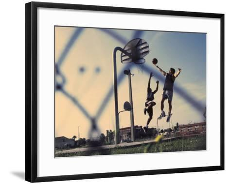 Low Angle View of Two Men Playing Basketball--Framed Art Print