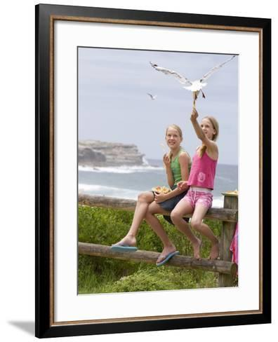 Two Girls Feeding Chips to a Seagull at the Beach-Louise Hammond-Framed Art Print