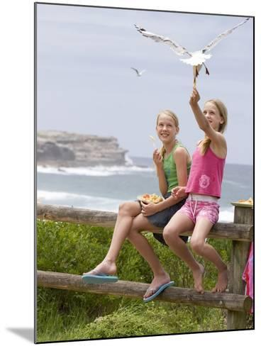 Two Girls Feeding Chips to a Seagull at the Beach-Louise Hammond-Mounted Photographic Print