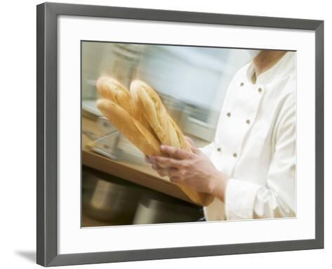 Chef Hurrying Through Kitchen with Baguettes--Framed Art Print
