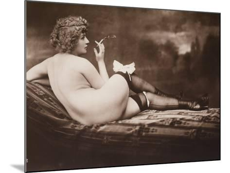 Portrait of a Young Woman Posing Naked, with Her Back Turned, as She Smokes a Cigarette--Mounted Photographic Print