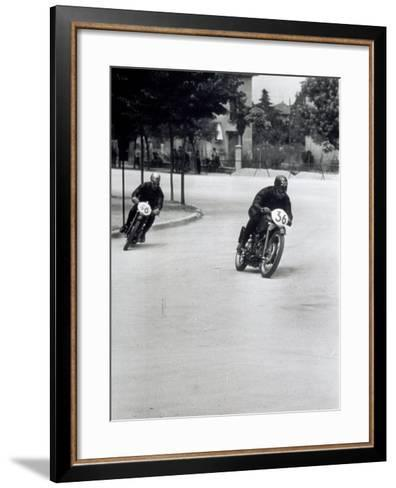 Two Motorcyclists Racing Along a Road, Otorcycles are Numbered 46 and 36-A^ Villani-Framed Art Print