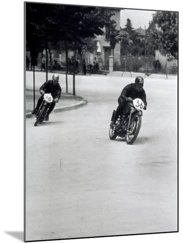 Two Motorcyclists Racing Along a Road, Otorcycles are Numbered 46 and 36-A^ Villani-Mounted Photographic Print