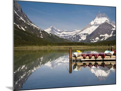Colorful Canoes Line the Dock at Many Glacier Lodge on Swiftcurrent Lake During Sunrise-Brad Beck-Mounted Photographic Print