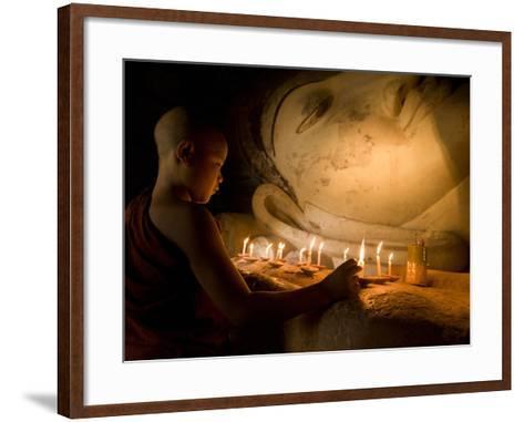 A Novice Monk Lighting Candles at a Massive Buddha Statue in Burma (Myanmar)-Kyle Hammons-Framed Art Print