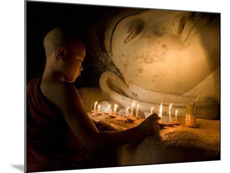 A Novice Monk Lighting Candles at a Massive Buddha Statue in Burma (Myanmar)-Kyle Hammons-Mounted Photographic Print