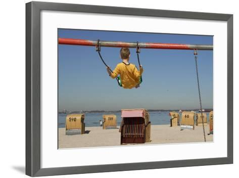 A Boy Plays on a Swing at the Beach of Laboe, Germany-Christian Hager-Framed Art Print