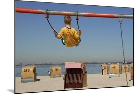 A Boy Plays on a Swing at the Beach of Laboe, Germany-Christian Hager-Mounted Photographic Print