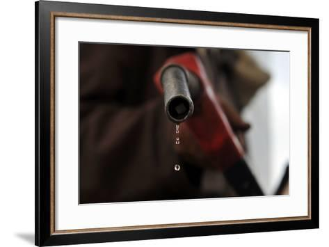 A Pump Attendant Holds a Fuel Nozzle at a Gasoline Station-Yahya Arhab-Framed Art Print