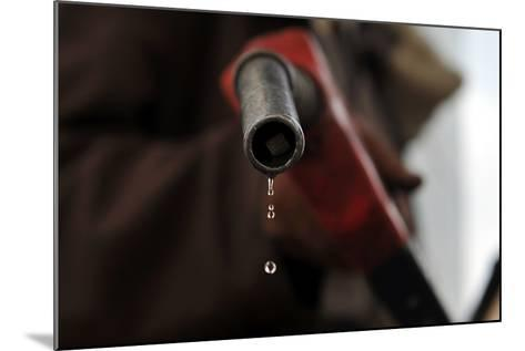 A Pump Attendant Holds a Fuel Nozzle at a Gasoline Station-Yahya Arhab-Mounted Photographic Print