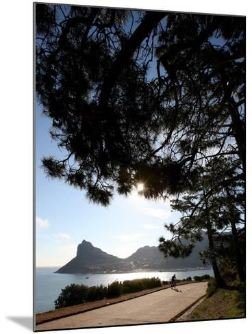 A Cyclist Rides Past the Sentinel Peak in Hout Bay Near Cape Town, South Africa-Jon Hrusa-Mounted Photographic Print