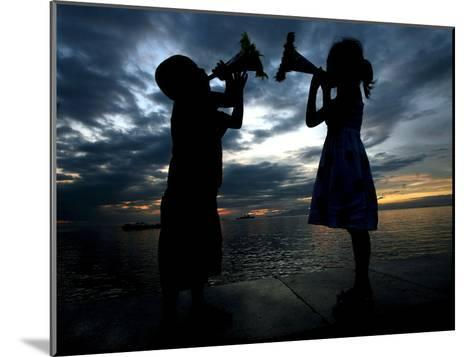 Two Children Sound their Toy Trumpets Along the Manila Baywalk in Manila, Philippines-Mike F. Alquinto-Mounted Photographic Print