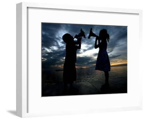 Two Children Sound their Toy Trumpets Along the Manila Baywalk in Manila, Philippines-Mike F. Alquinto-Framed Art Print