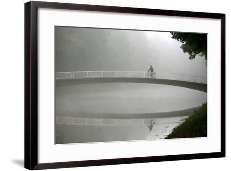 A Cyclists Rides His Bike over a Bridge at the Karlsaue Park in Kassel, Germany-Uwe Zucchi-Framed Art Print