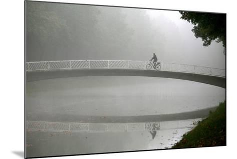 A Cyclists Rides His Bike over a Bridge at the Karlsaue Park in Kassel, Germany-Uwe Zucchi-Mounted Photographic Print