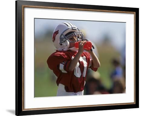 8 Year Old Boy Taking a Drink During a Football Game--Framed Art Print