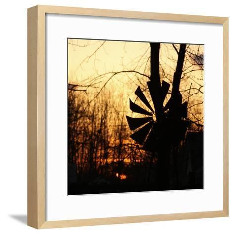 Windmill Silhouette Against Bare Branches and Sunset Sky-Anna Miller-Framed Art Print