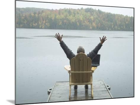 Man Sitting on a Dock with Arms Outstretched--Mounted Photographic Print