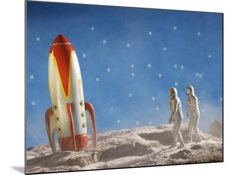 Astronaut Figurines Walking Towards Rocket--Mounted Photographic Print