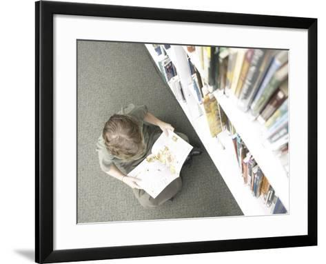 Little Boy Reading Book Beside Library Shelf--Framed Art Print