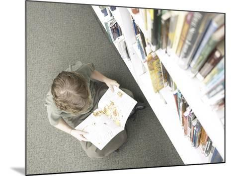 Little Boy Reading Book Beside Library Shelf--Mounted Photographic Print