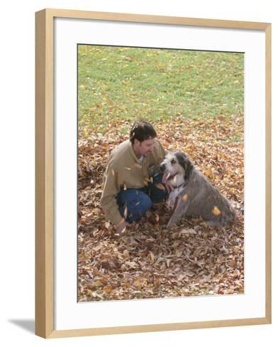 Man Playing with Dog in Autumn Leaves--Framed Art Print