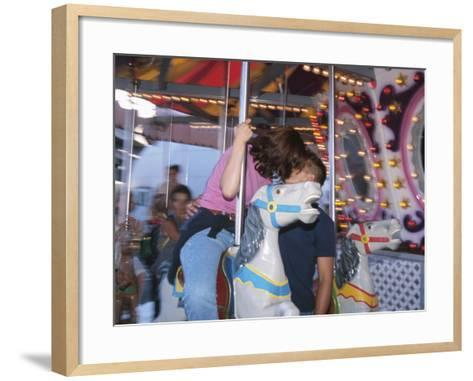 Young Couple Kissing on Carousel--Framed Art Print