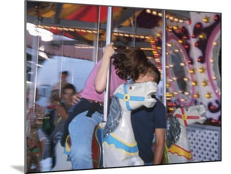 Young Couple Kissing on Carousel--Mounted Photographic Print