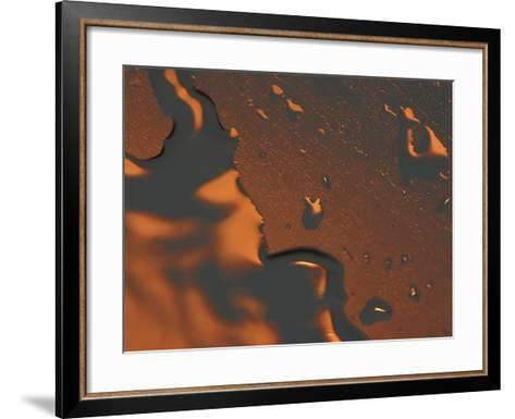 Close-up of Illuminated Orange Water Droplets and a Puddle on a Shiny Surface--Framed Art Print