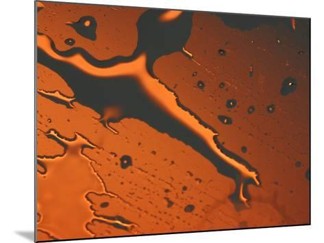 Close-up of Illuminated Orange Water Droplets and a Puddle on a Shiny Surface--Mounted Photographic Print