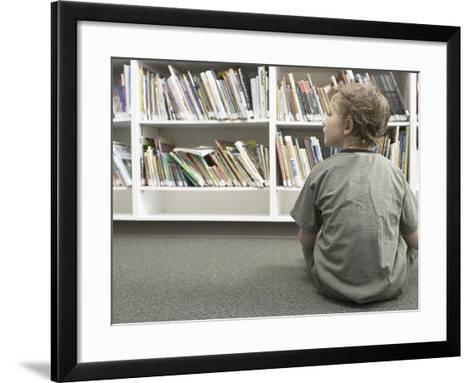 Little Boy Looking Rows of Books on Library Shelves--Framed Art Print