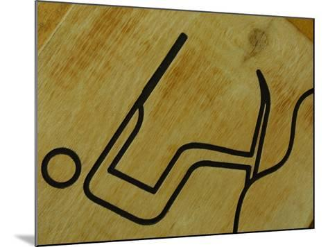 Close-Up of Wooden Tile with Water Skiing Figure--Mounted Photographic Print