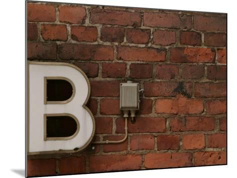 Florescent B Letter Light on Brick Wall--Mounted Photographic Print